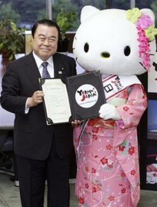 Kimono-clad Hello Kitty holds her certificate received from Japan's Land, Infrastructure, Transport and Tourism Minister Tetsuzo Fuyushiba, left, at his office in Tokyo, Monday, May 19, 2008. Fuyushiba appointed the popular cartoon character as ambassador to welcome tourists from China and Hong Kong. (AP Photo/Koji Sasahara)