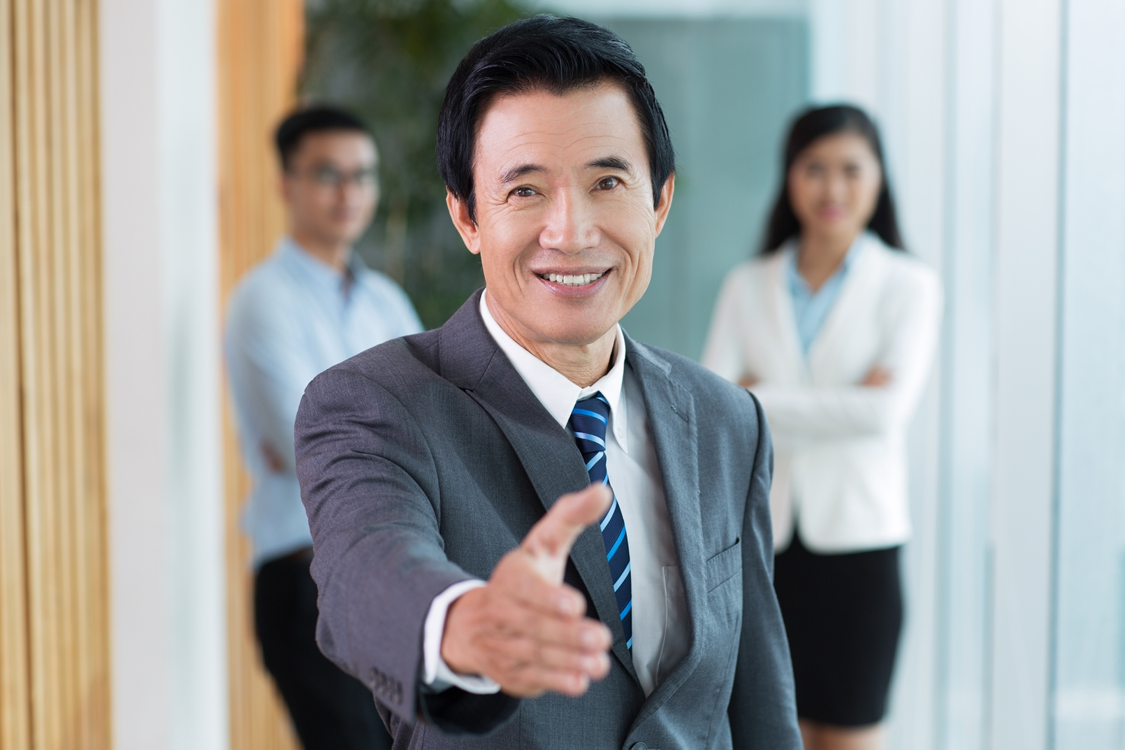 Smiling senior Asian businessman offering handshake