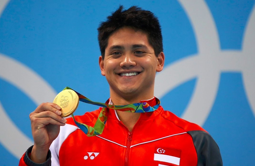 Joseph Schooling shows off his first gold medal.