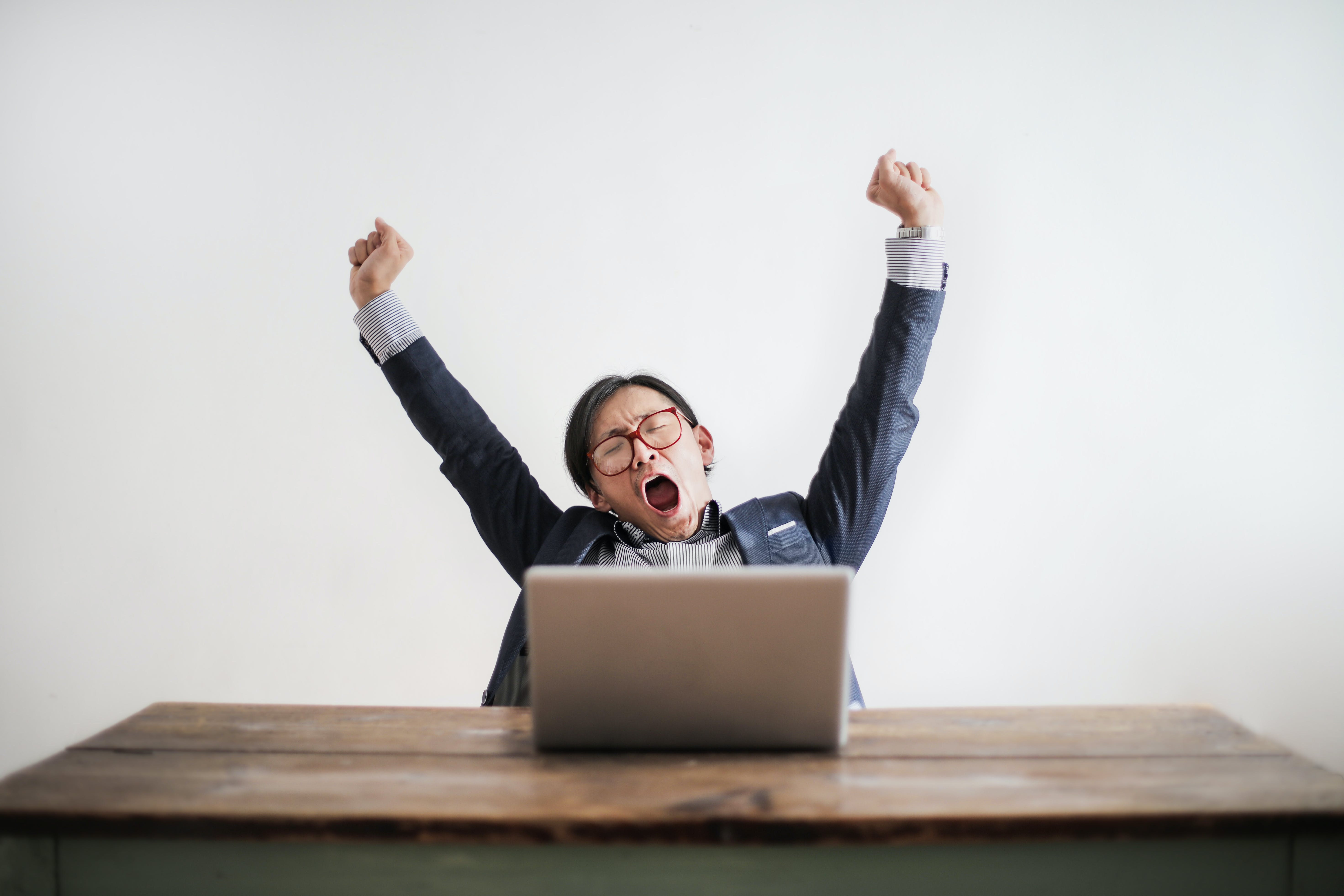 Photo of Yawning Man with His Hands Up and Eyes Closed Sitting at a Table with His Laptop
